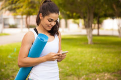 Yogaflicka med en mobiltelefon Royaltyfri Foto