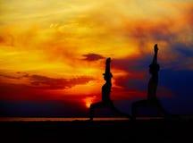 Yogafolket som utbildar och mediterar i krigare, poserar yttersidan vid stranden på soluppgång eller solnedgången Arkivfoton