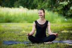 Yogafrau auf grünem Gras beim Lotoshaltungslächeln Stockfotografie
