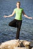 Yogafrau, die auf einem Fahrwerkbein durch Wasser steht Stockfotos