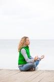 Yogafrau, die auf hölzerner Brücke nahe dem Ozean sitzt Stockfoto