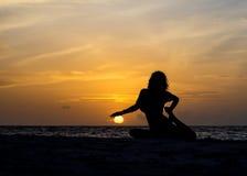 Yogafrau, die auf Seeküste sitzt Stockfoto