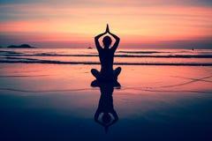 Yogafrau, die auf Seeküste am Sonnenuntergang sitzt Reise Stockbild
