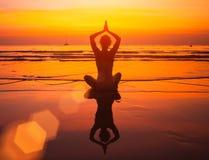 Yogafrau, die auf Seeküste am Sonnenuntergang sitzt nave Lizenzfreies Stockfoto