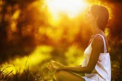 Yogafrau, die bei Sonnenuntergang meditiert Stockbild