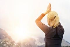 Yogafrau, die in der schönen Naturberglandschaft bei Sonnenuntergang oder Sonnenaufgang meditiert Stockbilder