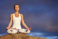 Yogafrau, die draußen meditiert Stockbilder