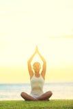 Yogafrau, die durch Meer sich entspannt Stockfoto