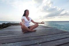 Yogafrau, die nahe Meer meditiert Stockbild