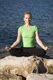 Yogafrau, die sich durch Wasserhände hinsitzt Stockfotografie