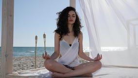 Yogafrau im Bungalow, auf Hintergrundmeer und Sand, Sommer, Wind entwickelt Haar und weißen Stoff, auf Tropeninseln stock video