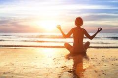 Yogafrau im Lotussitz, der auf einem Seestrand sitzt Stockfotografie