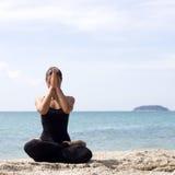 Yogafrau wirft auf Strand nahe Meer und Felsen auf Lizenzfreies Stockbild
