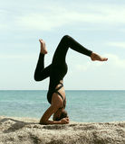 Yogafrau wirft auf Strand nahe Meer und Felsen auf Lizenzfreie Stockbilder