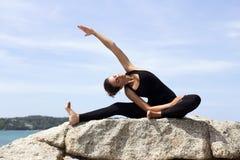 Yogafrau wirft auf Strand nahe Meer und Felsen auf Stockfoto