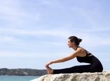 Yogafrau wirft auf Strand nahe Meer und Felsen auf Lizenzfreies Stockfoto