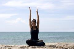 Yogafrau wirft auf Strand nahe Meer und Felsen auf Stockfotos