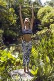 Yogafrau wirft in den Tropen auf, die stilvolle Sportkleidung tragen Phuket-Insel, Thailand Stockfotos