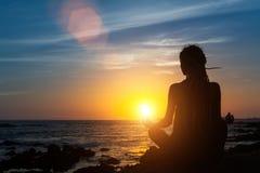 Yogafrauenschattenbild auf dem Ozean während des erstaunlichen Sonnenuntergangs relax lizenzfreie stockbilder