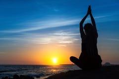 Yogafrauenschattenbild auf dem Ozean während des Sonnenuntergangs relax stockbild