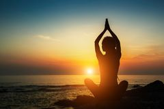 Yogafrauenschattenbild Meditation auf dem Ozean relax stockfotografie