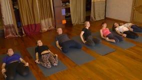 Yogagrupp av folk som övar sund livsstil i konditionstudioyoga arkivfilmer