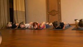 Yogagrupp av folk som övar sund livsstil i konditionstudioyoga lager videofilmer