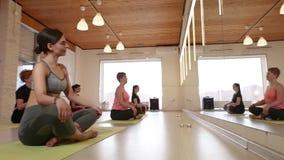 Yogagrupp, grupp människor som kopplar av och gör yoga arkivfilmer