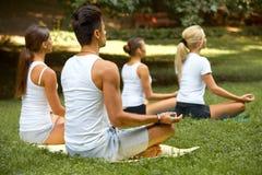 Yogagrupp Grupp människor som mediterar på sommar, parkerar fotografering för bildbyråer