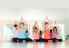 Yogagrupp i studiorum, grupp människor som gör det placerade trädet, poserar Arkivbild