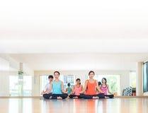 Yogagrupp i studiorum, grupp människor som gör lotusblomma, poserar med Arkivfoton