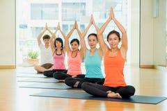 Yogagrupp i studiorum, grupp människor som gör namaste, poserar intelligens Royaltyfria Bilder