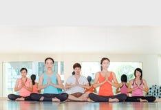 Yogagrupp i studiorum, grupp människor som gör namaste, poserar intelligens Arkivbilder