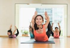 Yogagrupp i studiorum, grupp människor som gör pilbågen, poserar, stretc Royaltyfria Foton