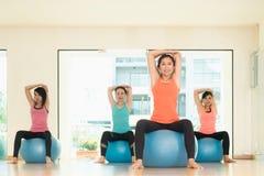 Yogagrupp i studiorum, grupp människor som gör yoga, poserar med t Royaltyfri Foto