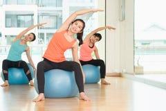 Yogagrupp i studiorum, grupp människor som gör yoga, poserar med t Arkivbild