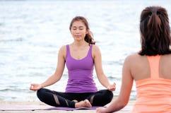 Yogagrupp på havsstranden, den ledar- gurun som gör lotusblomma, poserar med musslan Arkivfoton