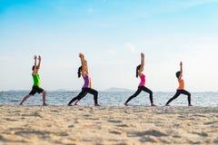 Yogagrupp på havsstranden i solnedgångtid, grupp människor som gör Wa arkivfoto