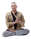 Yogaguru som spelar flöjten som isoleras på vit Royaltyfri Bild