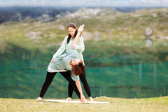 Yogainstructor gives assistance Royalty Free Stock Photo