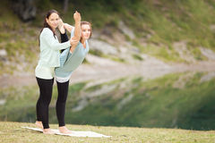 Yogainstructor gives assistance Stock Images