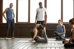 Yogainstruktör som utför avancerad övning för rajabhudjangasana royaltyfri bild