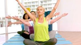 Yogaklasse die hun handen opheffen stock video