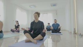 Yogaklasse van midden oude vrouwen en de mens wordt gemaakt die in lotusbloempositie mediteren in een geschiktheidsstudio die - stock videobeelden
