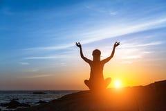 Yogakontur Meditationkonditionkvinna på havsstranden under fantastisk solnedgång arkivbilder