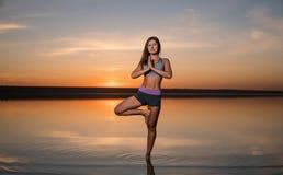 Yogakvinna på stranden på solnedgången arkivbild