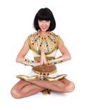 Yogakvinna som ha på sig en egyptisk dräkt. Arkivfoto
