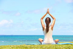 Yogakvinna som kopplar av vid havet arkivbild
