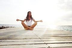 Yogakvinna som mediterar nära havet Royaltyfria Foton