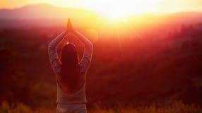 Yogakvinna som mediterar p? solnedg?ngen arkivfoton